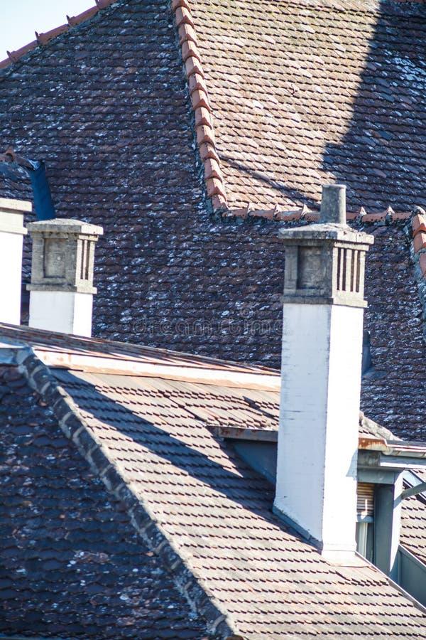 Detail von hohen schmalen Kaminen auf einem mit Ziegeln gedeckten Dach lizenzfreie stockfotos