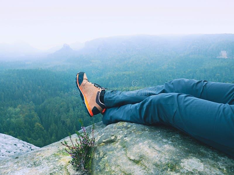 Detail von Wandererbeinen im schwarzen orange Wanderstiefel auf Gebirgsgipfel Füße in den Trekkingsschuhen lizenzfreie stockbilder