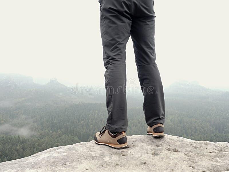 Detail von Wandererbeinen im schwarzen orange Wanderstiefel auf Gebirgsgipfel Füße in den Trekkingsschuhen lizenzfreie stockfotos