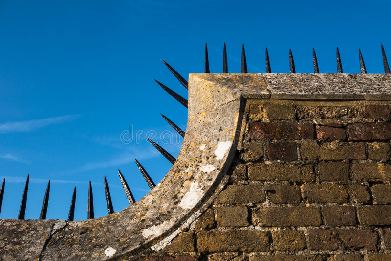 Detail of wall with row of sharp spikes along edge. Detail close-up of Tudor era brick wall with a row of sharp black spikes on top edge royalty free stock photography