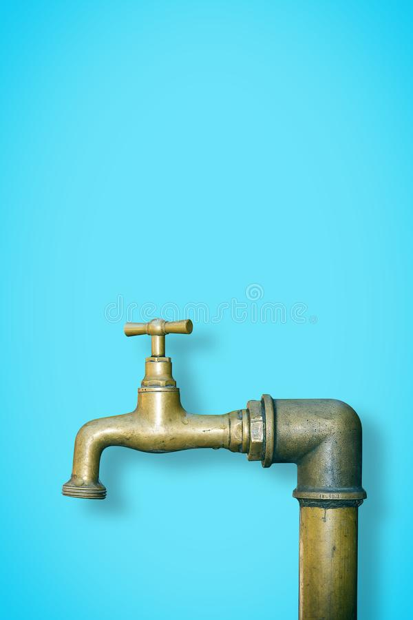 Detail of a water brass faucet  on solid color background - image with copy space.  stock photo