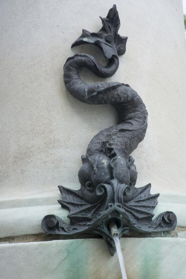 Fountain detail of serpent waterspout. A detail of a waterspout spewing water into a fountain. made of metal, the spout is bolted onto the fountain royalty free stock image