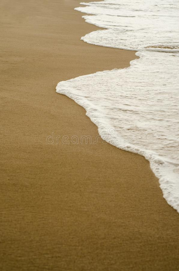Detail of waves on the shore with reflections of clouds, vertical photography. Summer travel in the sea stock photography