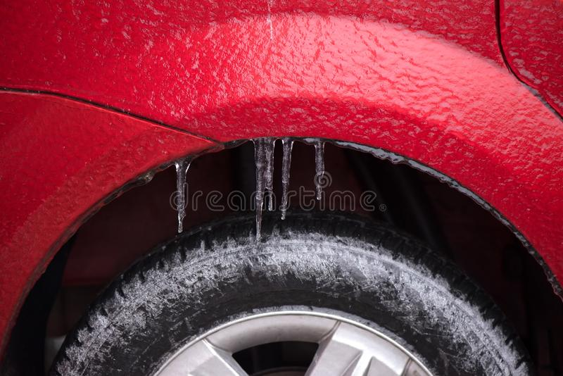 Detail of the wheel of a frozen car. With icicles after a freezing rain phenomenon stock photography
