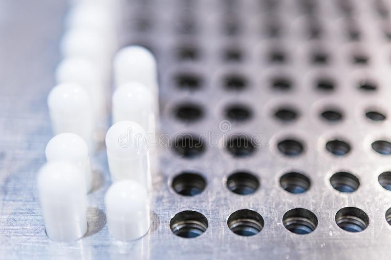 White medical pills on pharmacy equipment machine royalty free stock image