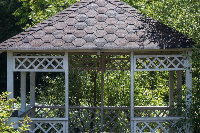Detail of white summerhouse surrounded by green trees stock photos