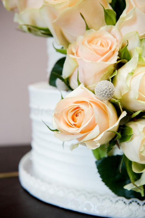Detail of White Wedding Cake With Peach Roses and Lace. A close-up of a white tiered wedding cake featuring a luscious bouquet of peach roses with green trims royalty free stock images