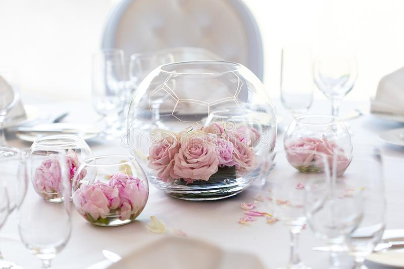 Detail of white wedding table set-up with fresh pink roses in glass bowls and rose petals. Blurry background royalty free stock images