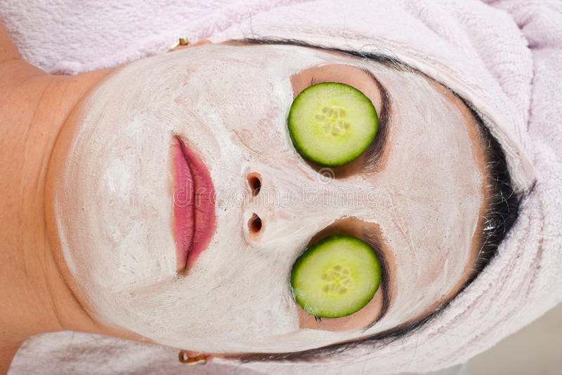 Detail of woman with facial mask and cucumber royalty free stock images