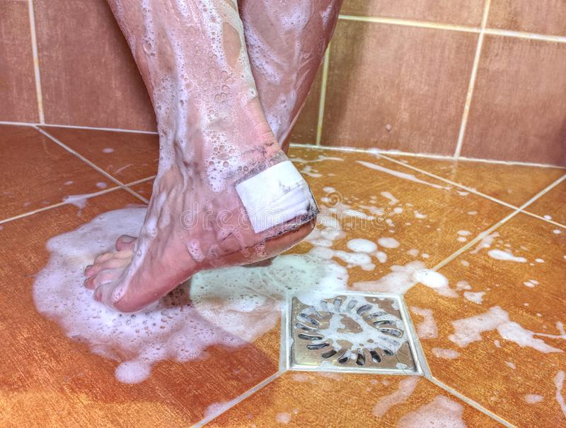 Detail of woman foot on bathroom tiles. Evening hygiene after long workday young wet wellness water stainless steel sport body skin showerhead rust real life royalty free stock images