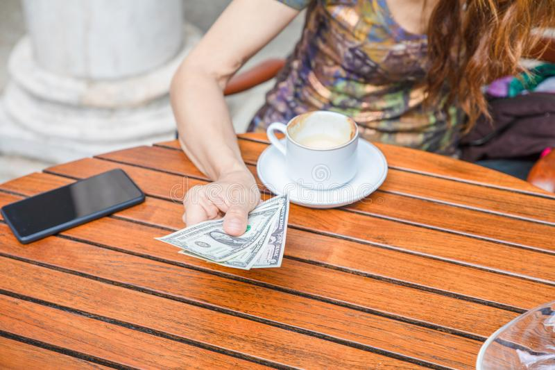 Detail of woman hand paying with dollar bills a coffee cup on table royalty free stock photography