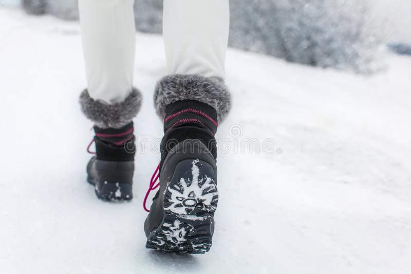 Detail of woman lifting her black and gray snow boot. With faux fur and purple laces, showing tread of the boots, shot on winter overcast day royalty free stock images