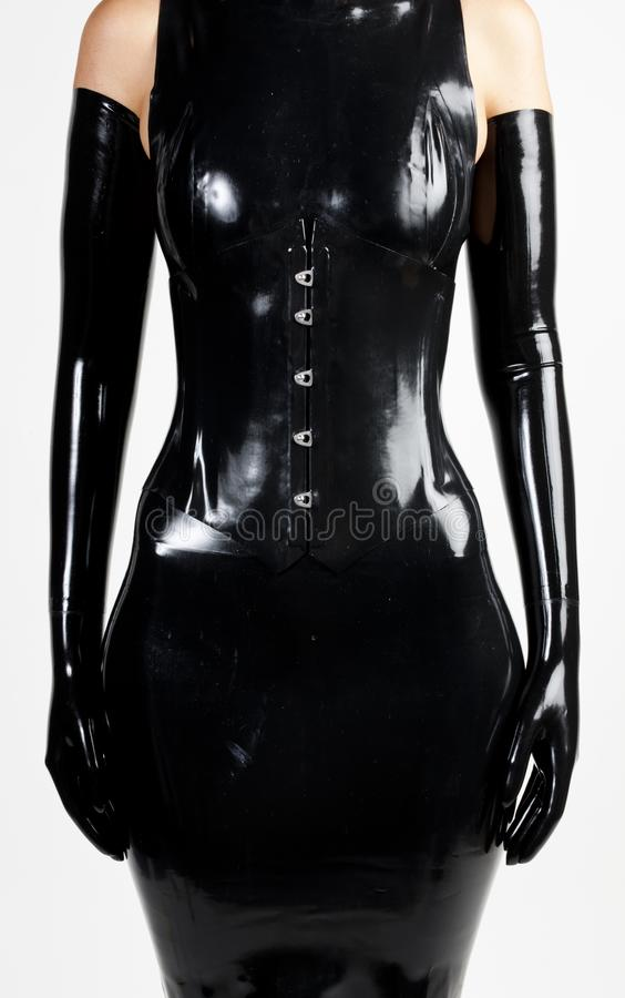 Detail of woman wearing latex clothes. Inside, indoors, interiors, person, persons, people, women, female, adult, one, standing, dress, corset, gloves, fashion stock images