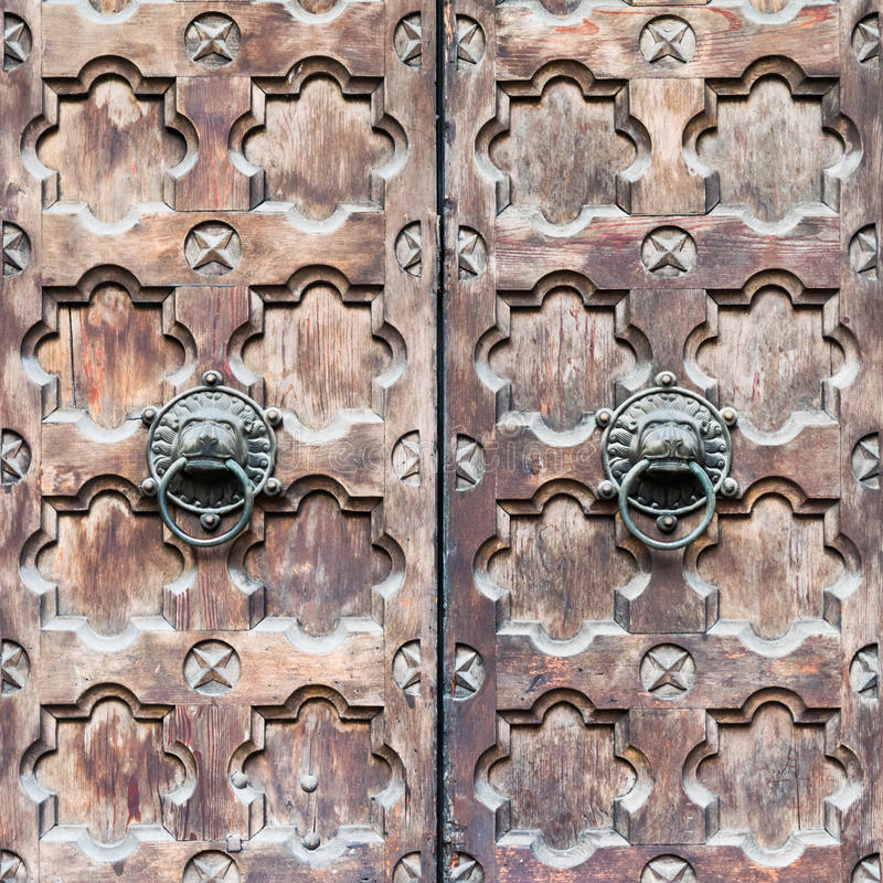 Detail of a wooden door with two knocker shaped a lion's head. royalty free stock photo