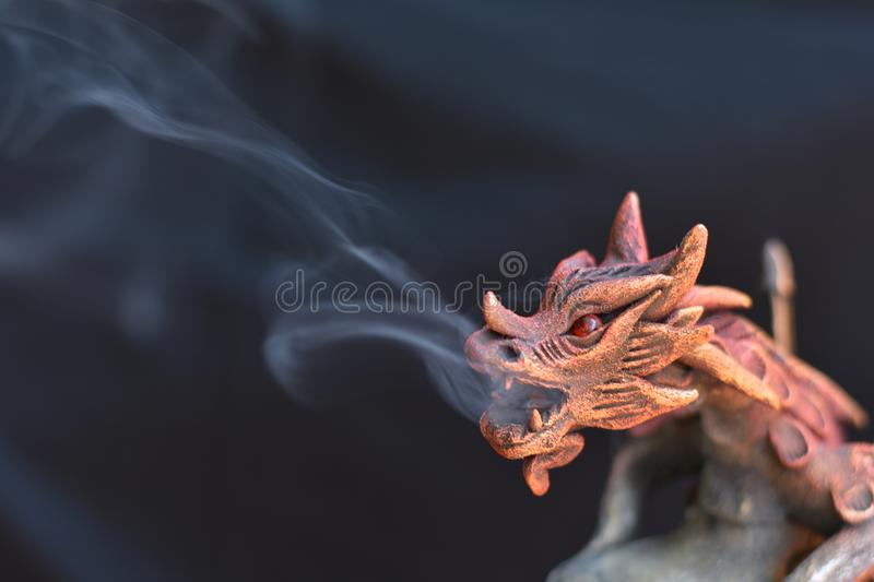 Detail of wooden incense burner in the shape of a dragon breathing smoke royalty free stock images