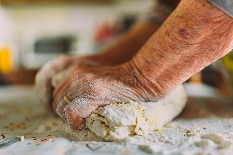 wrinkled old woman's hands making italian pasta stock image
