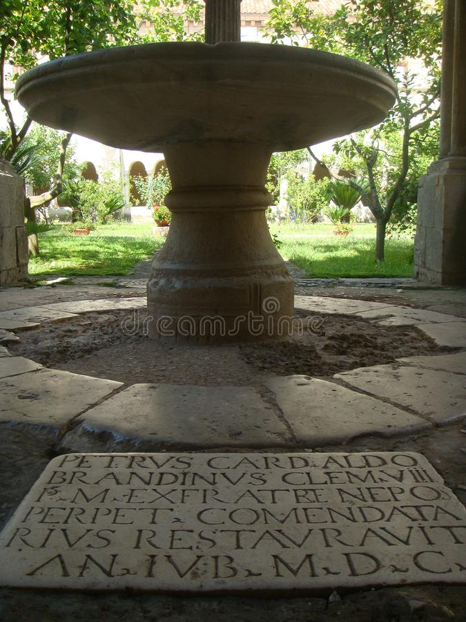 Detail of writings in Latin engraved in a stone with behind a table of marble in the cloister of the Abbey of Fossanova in Italy stock photos