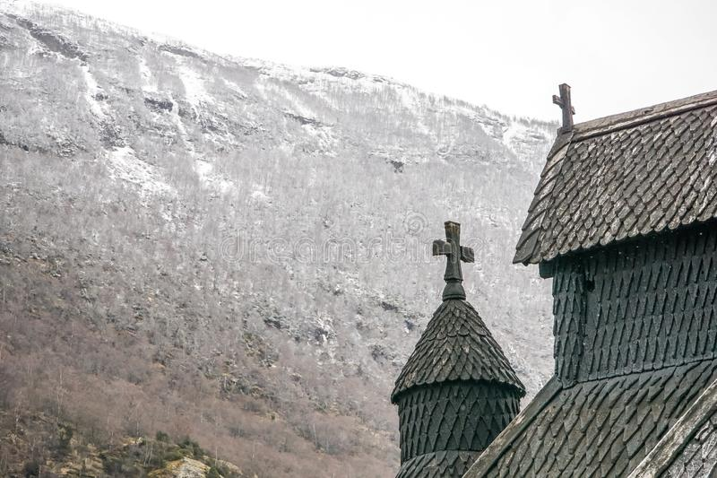 Detail of 1000 year old intricate stave church in Norway with snow-covered mountain in background royalty free stock images