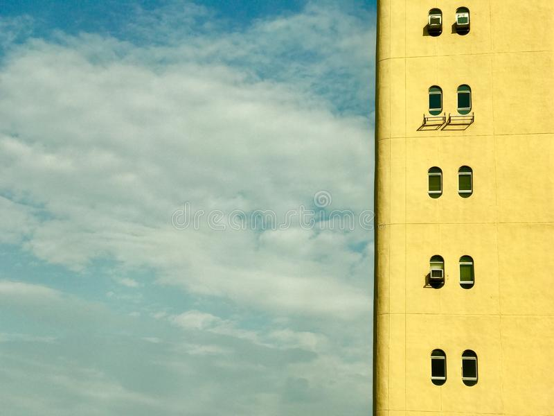 Detail of yellow building with oval windows and cloudy blue sky stock image