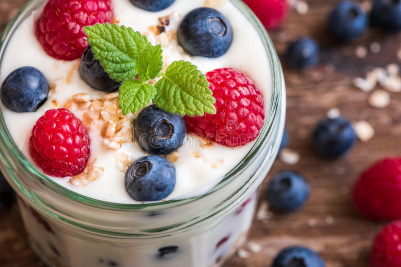 Detail of Yogurt with Fresh Berries on Woden Table royalty free stock images