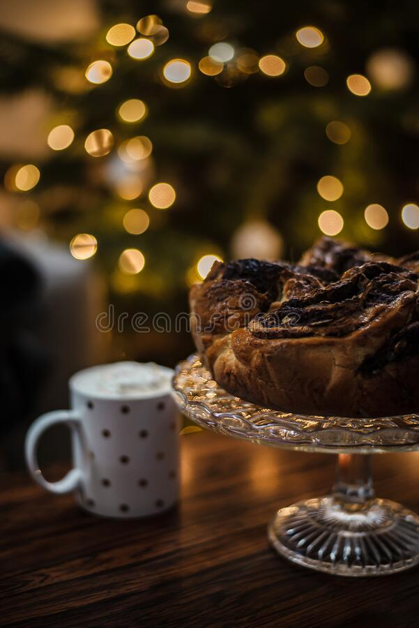 Detail of yummy comfort homemade food in front od a christmas tree. Enjoy chocolate wreath with hot chocolate with whipped cream. royalty free stock photos
