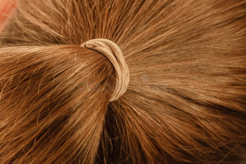 Detailed closeup of brown hair in ponytail. Detailed close up of brown, dark blonde hair in ponytail with band. Hairdo surface stock images