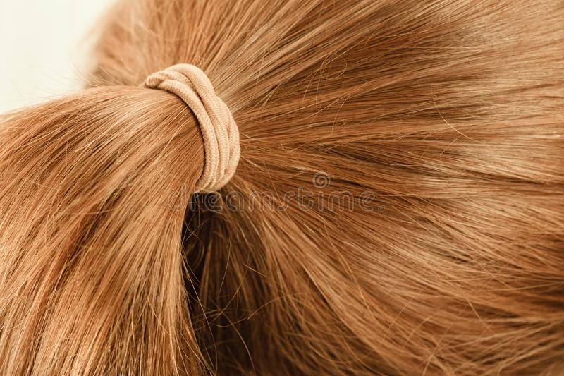 Detailed closeup of brown hair in ponytail. Detailed close up of brown, dark blonde hair in ponytail with band. Hairdo surface royalty free stock photos