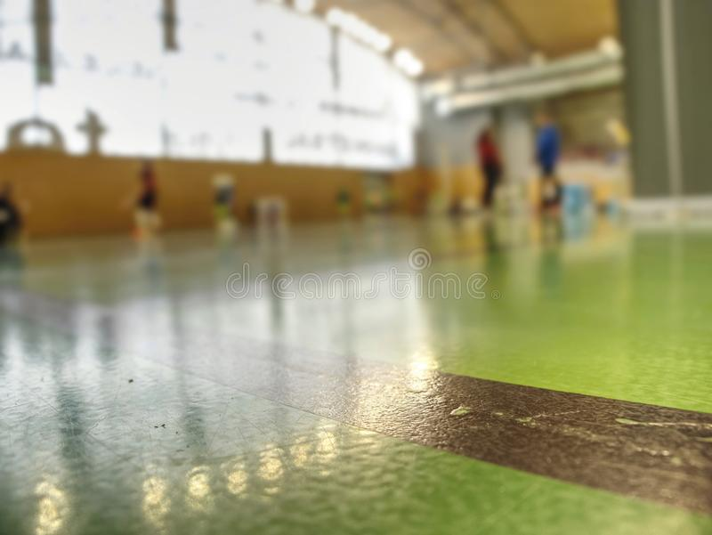 Detailed green floor in a school gymnasium, players out of focus royalty free stock photo