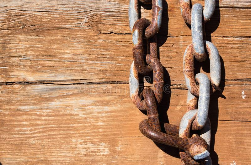 Wood board with iron chain link. Rusted chain hangin in front of a wooden background. Steel chain. Industrial detailed background stock image