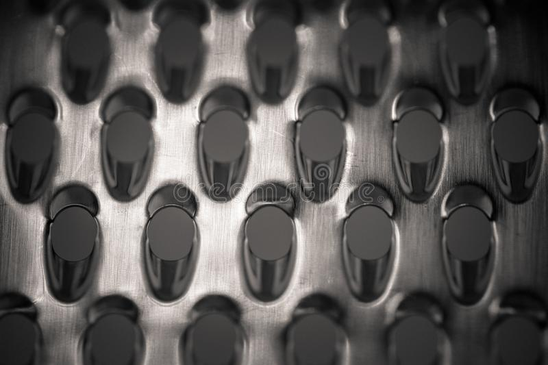 Detailed monocrome macro shot of a metal cheese grater. Kitchen stock photography