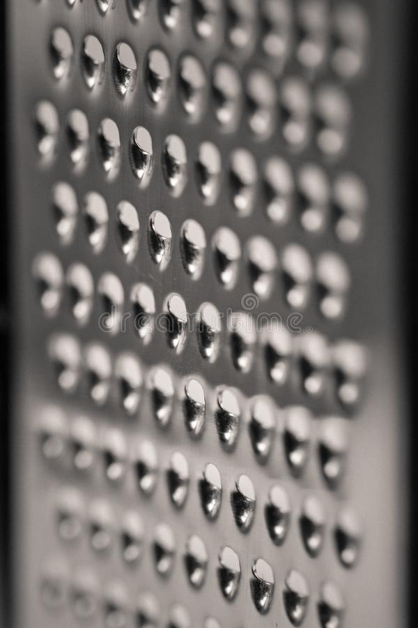 Detailed monocrome macro shot of a metal cheese grater. Kitchen royalty free stock photography