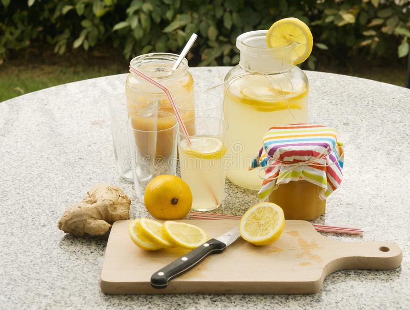 Detailed Picture of all ingredients neccesary to cook a homemade lemonade consist from water, lemon, ginger and glass of honey. Pitcher, chopping board royalty free stock image