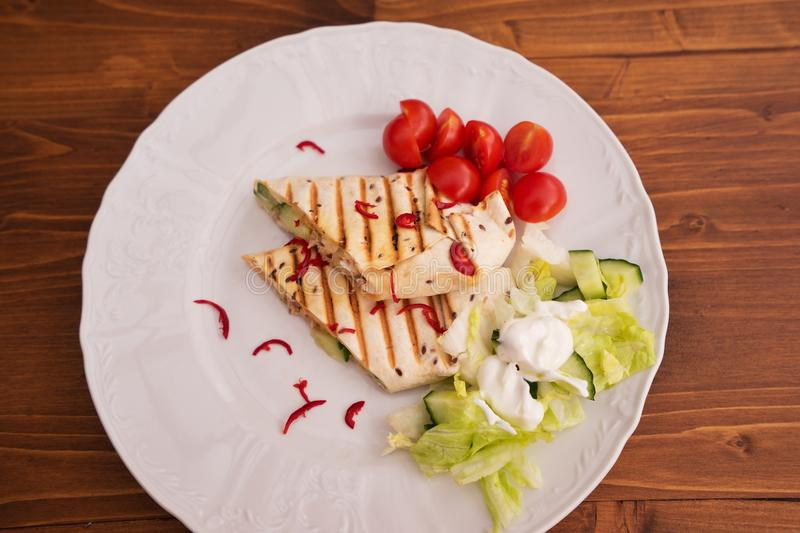 Detailed Picture of baked wraps, fachitas or burrito with fresh chili pieces, cherry tomatoes and fresh salad with cream stock image