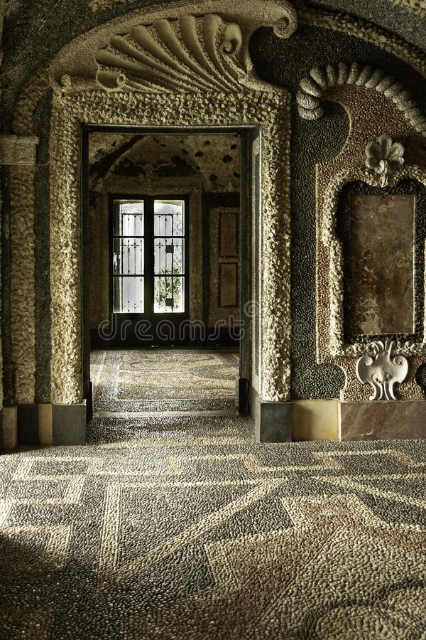 Indoor room of historic white & black pebbled floor, walls and ceiling with geometric patterns from Palace northern Italy royalty free stock photos