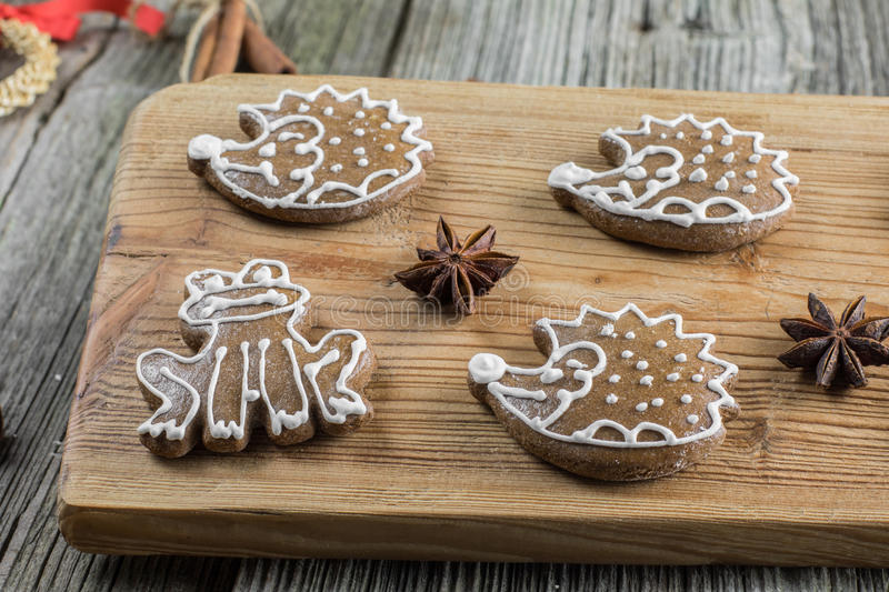 Detailed view on christmas gingerbread frog and hedgedog with st. Ar anise on wooden board stock photography