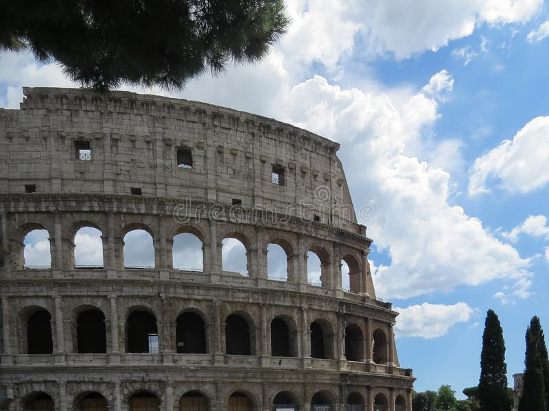 Detailed view of the exterior wall of the Colosseum in Rome against a blue cloudy sky stock images