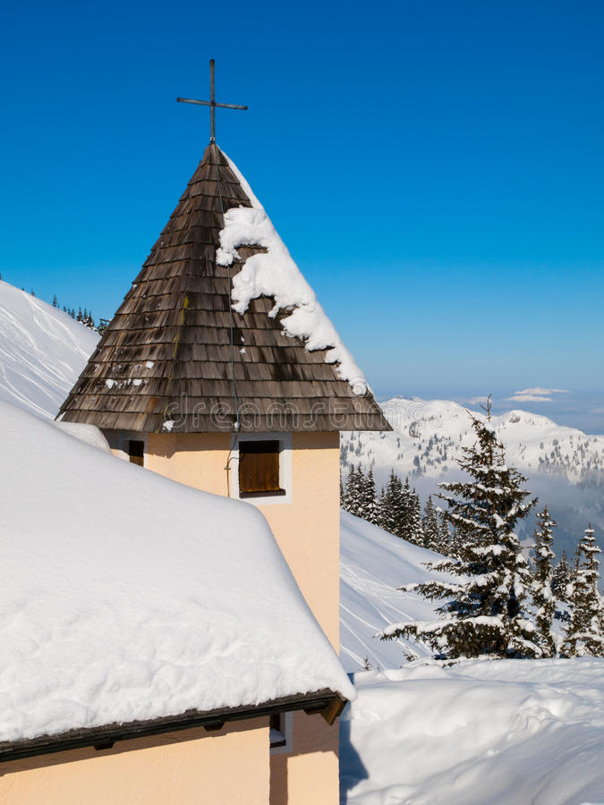 Detailed view of rural mountain church tower with cross on the top in snowy winter alpine landscape royalty free stock image
