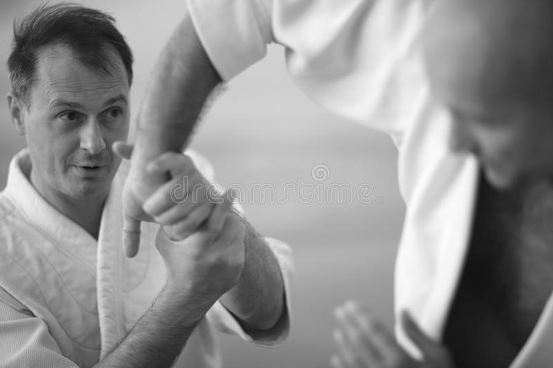 Details of aikido technique. Man controling his partner; gentle combat concept royalty free stock photos