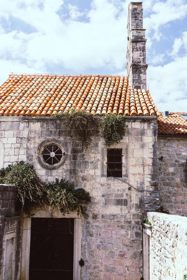 Details of an ancient building in the old town of Budva. Montenegro. Stone church with grass. round stained glass window covered stock photo