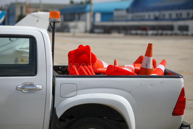 Details with the back of a truck carrying orange traffic safety cones on the runway of an airport royalty free stock photography