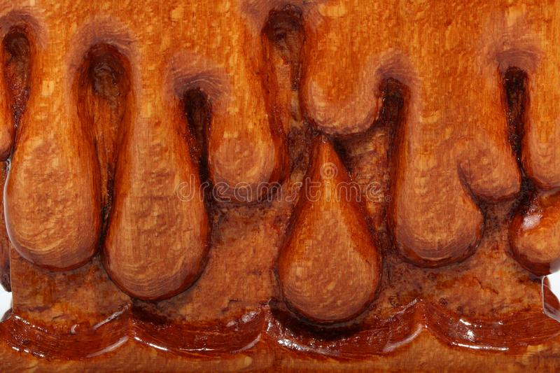 Details of base of an brown wooden candlestick with carved droplets in form of melted wax. Abstract background. Details of base of an old brown wooden stock photography