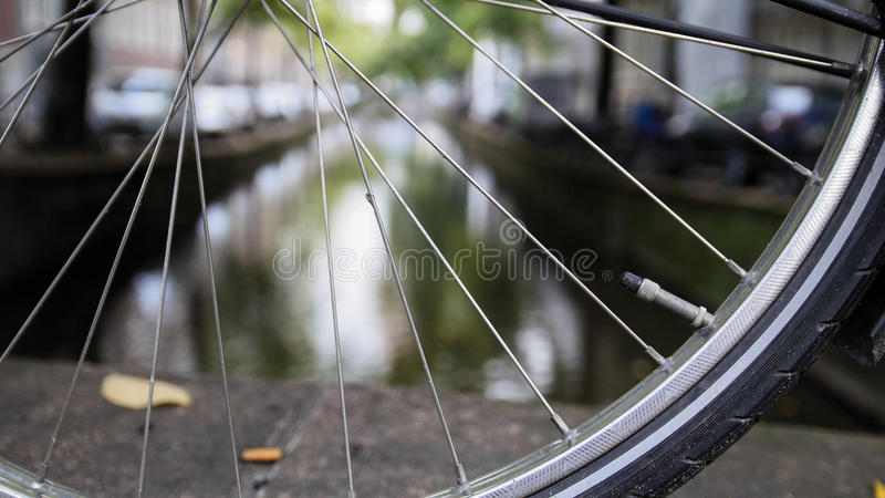 Details of bicycle wheel at Amsterdam canal, Autumn, Netherlands. Wide angle stock image
