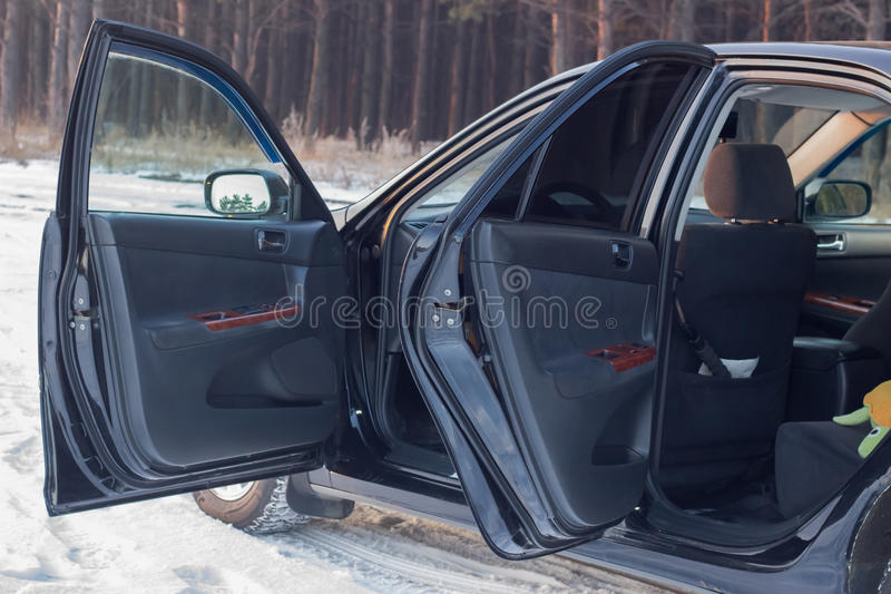 Details of the black car in the cabin, steering wheel, trunk, speedometer and open doors royalty free stock photo