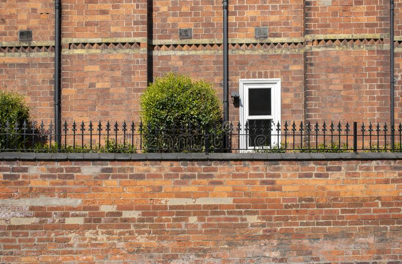 Details of a brick wall of a building, with a small window with white frame. royalty free stock image