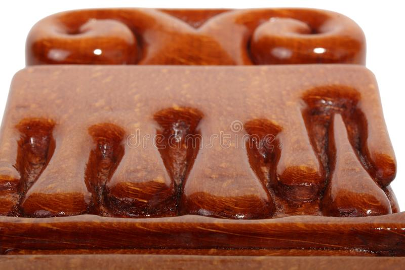 Details of an brown wooden candlestick without candle with carved droplets in form of melted wax. Isolated on a white. Details of an old brown wooden candlestick stock photo