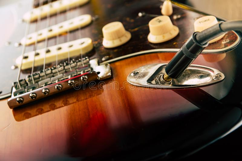 Details and connection of guitar and wire cable jack. Tone and volume controls. On sunburst guitar.Close up guitar royalty free stock photos