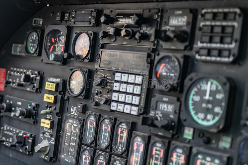 Details of control panel in military helicopter cockpit. Altitude and other major instruments on the panel of a military cockpit. Black metal frames and glowing stock photo