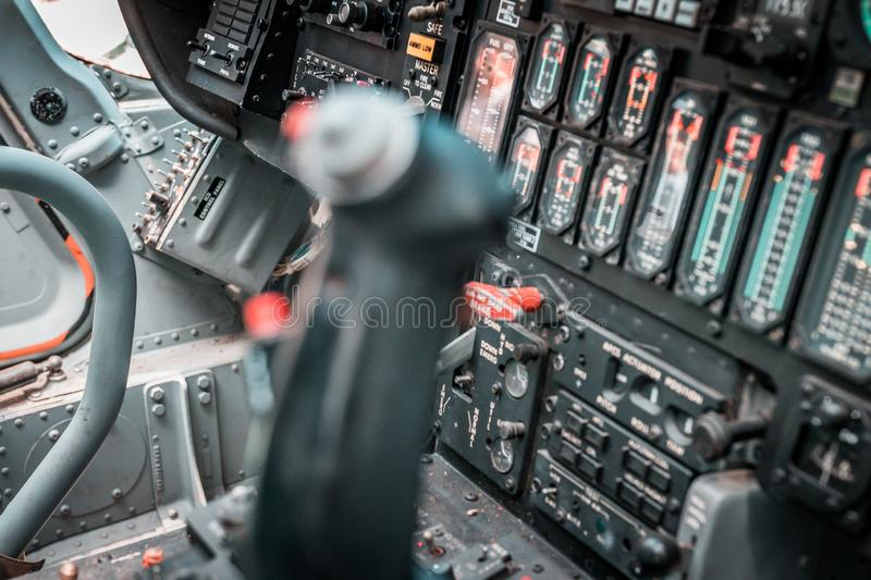 Details of control panel in military helicopter cockpit. Altitude and other major instruments on the panel of a military cockpit. Black metal frames and glowing royalty free stock image