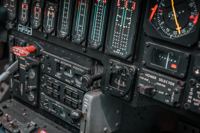 Details of control panel in military helicopter cockpit. Altitude and other major instruments on the panel of a military cockpit. Black metal frames and glowing stock images