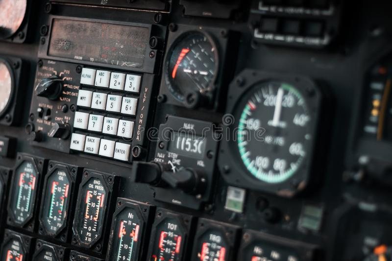 Details of control panel in military helicopter cockpit. Altitude and other major instruments on the panel of a military cockpit. Black metal frames and glowing stock photos